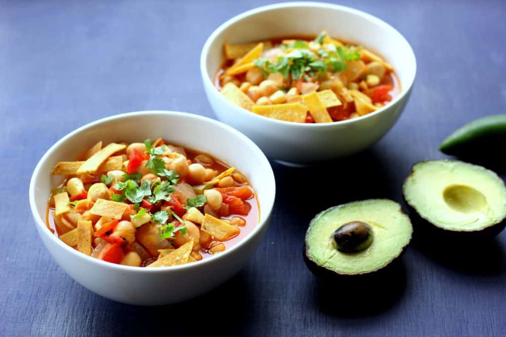 chickpea tortilla soup in bowls next to avocado