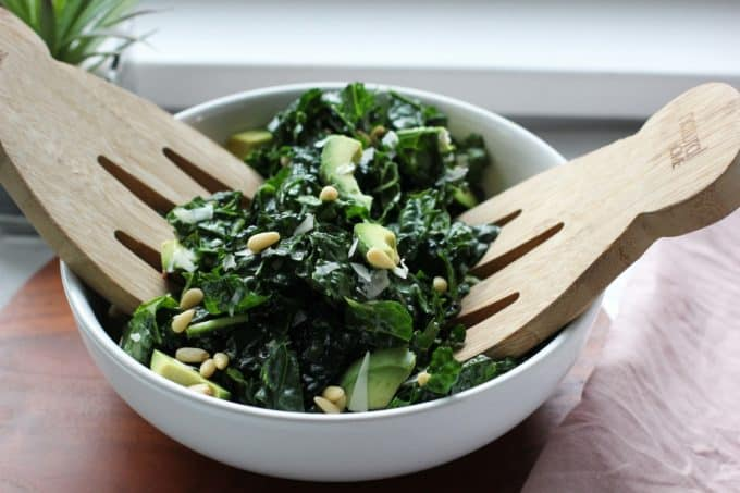 Kale salad in a bowl with salad tongs