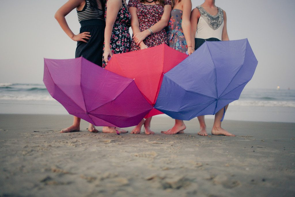 girls with umbrellas at the beach
