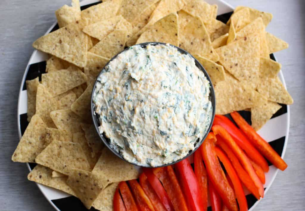 spinach dip on a plate with chips and peppers