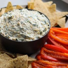 Spinach dip in a bowl with chips and peppers