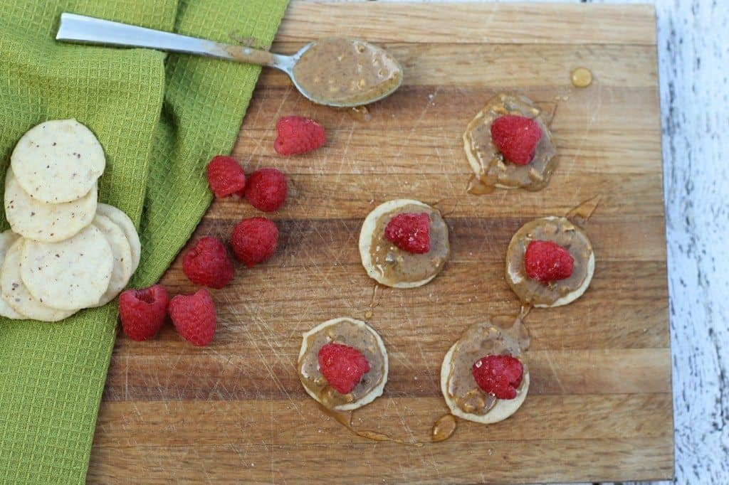 almond butter and raspberries on a cutting board