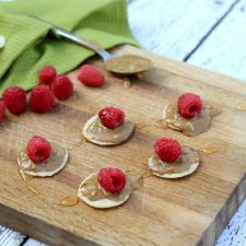 Try this super simple snack! It's just raspberries with almond butter and honey on a cracker!