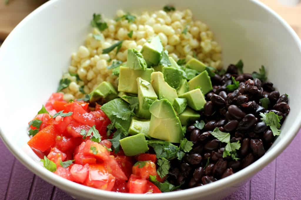 Ingredients for black bean and corn salad in a white bowl