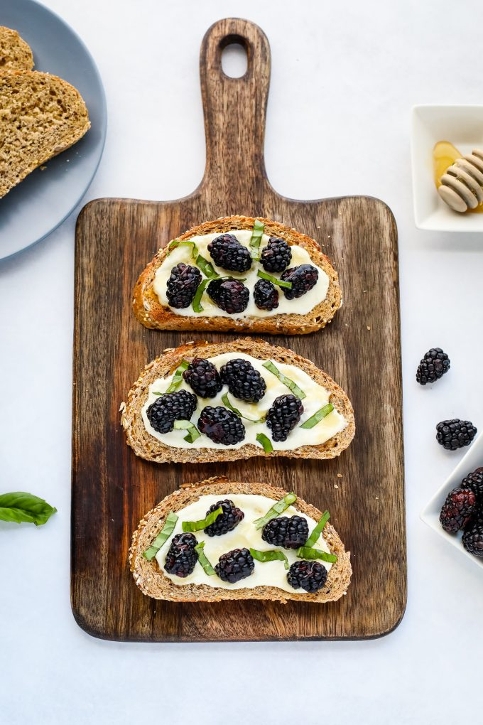 blackberry ricotta toast on a cutting board