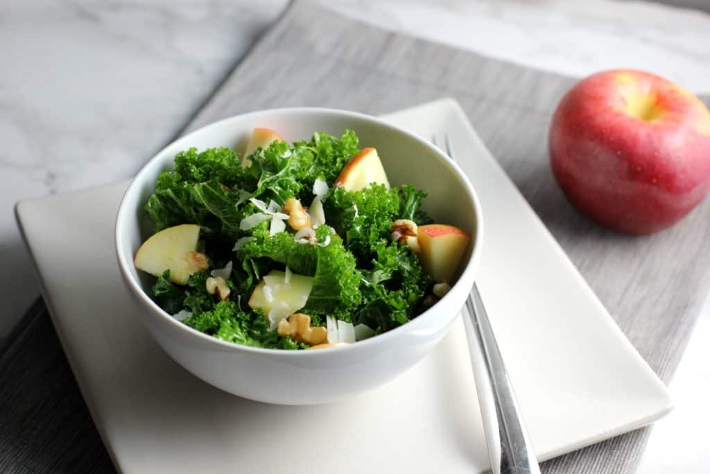 kale salad in a bowl next to an apple