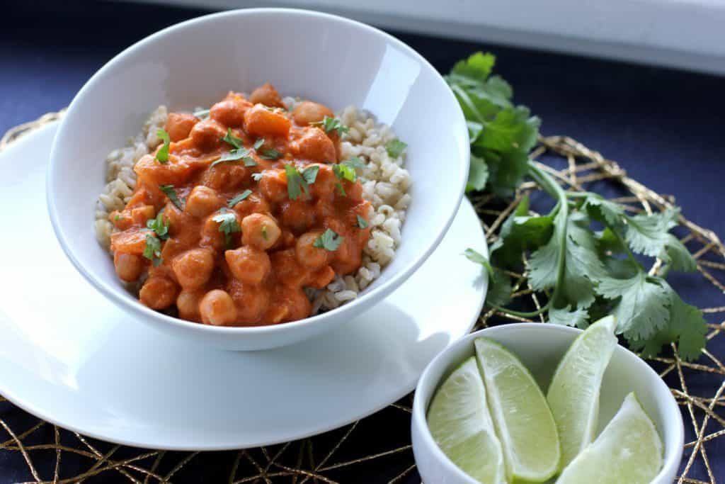 chickpea curry in a bowl with cilantro and lime