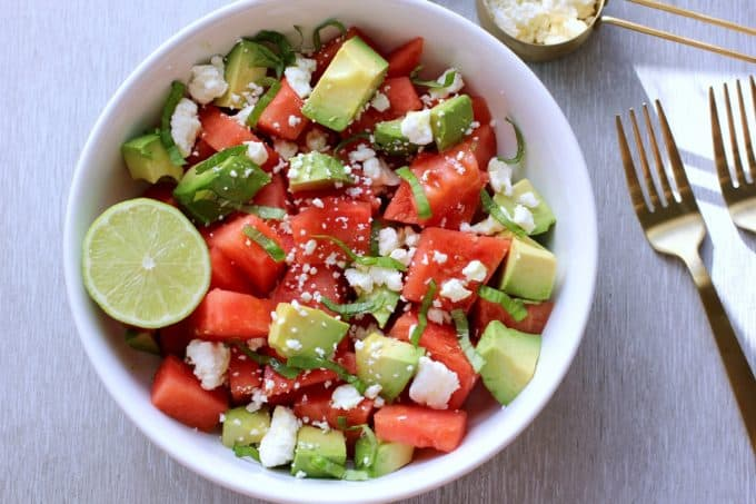 watermelon and avocado in a bowl with a gold fork on the side
