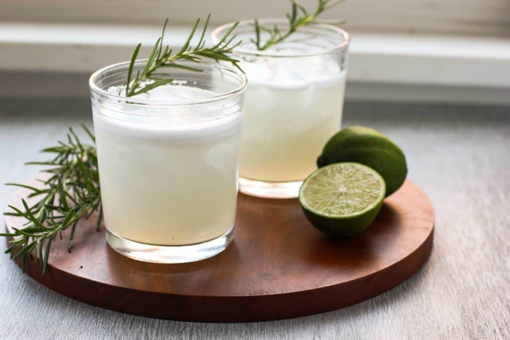 cocktails with rosemary next to a lime