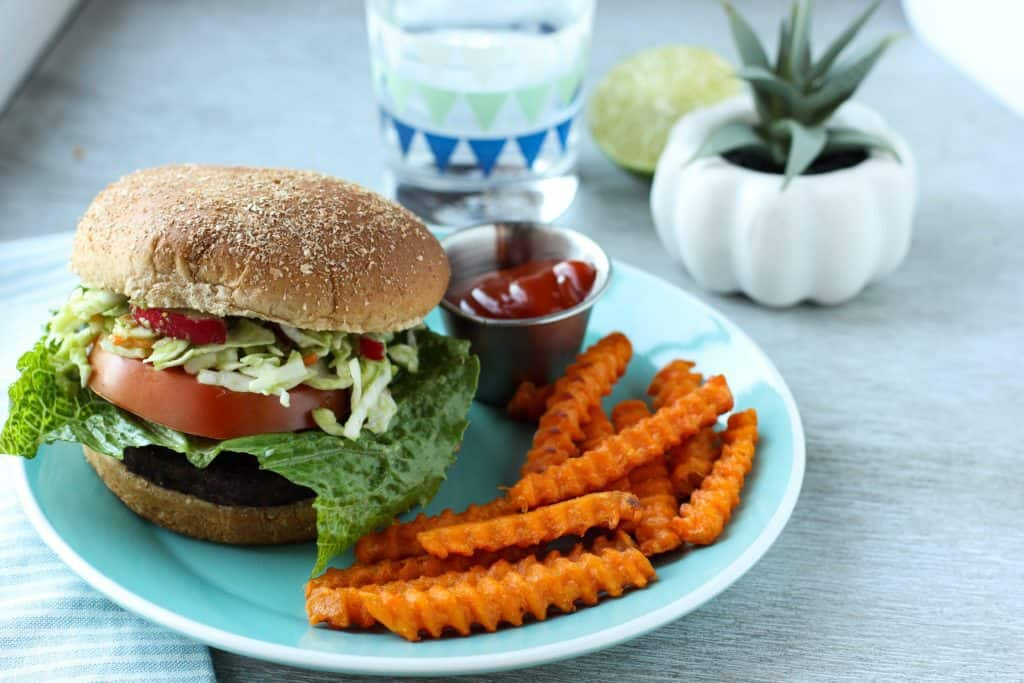 burger on a plate with sweet potato fries
