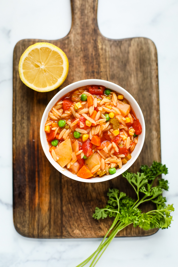 orzo vegetable soup in a bowl on a cutting board