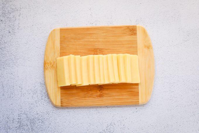 cheddar slices on a cutting board